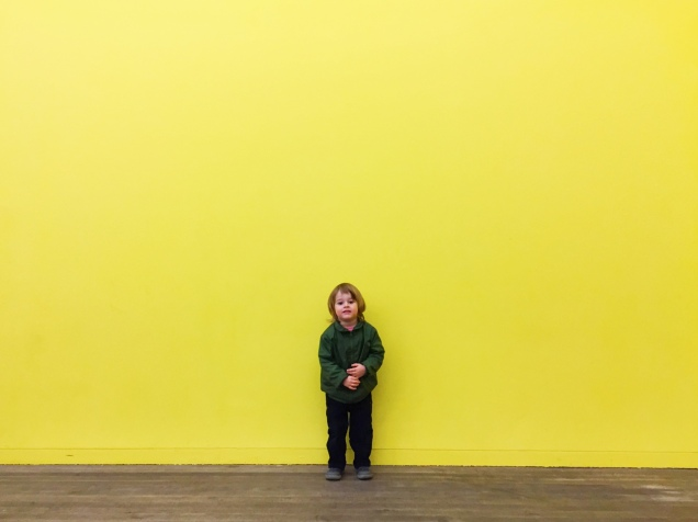 A child by a yellow wall.