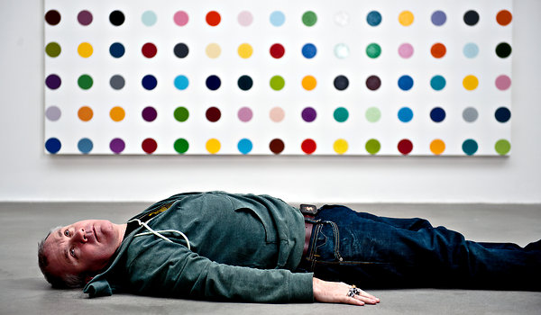 Damien Hirst in front of one of his spot paintings (that he probably didn't paint) in 2011.