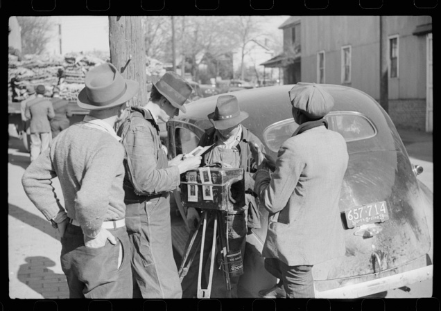 Travelling photographer making a sale outside warehouse where tobacco auctions are being held. Durham, North Carolina. Marion Post Wolcott, November 1939.