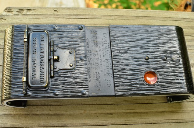 Various patent dates are etched into the case when you slide it open.  Also notice the large round protrusion above and to the right of the red window, this is what you press to open the camera.
